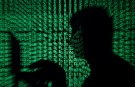 A man holds a laptop computer as cyber code is projected on him in this illustration picture taken on May 13, 2017. Capitalizing on spying tools believed to have been developed by the U.S. National Security Agency, hackers staged a cyber assault with a self-spreading malware that has infected tens of thousands of computers in nearly 100 countries. REUTERS/Kacper Pempel/Illustration - RTX35OS0