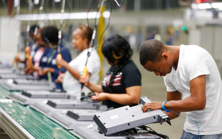 Workers on the assembly line replace the back covers of 32-inch television sets.