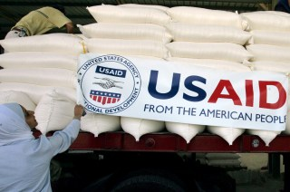 U.S. embassy staff hang a banner on a truck loaded with humanitarian aid before it is sent to Lebanon from Amman, Jordan August 31, 2006. The United States, through the Agency for International Developments (USAID), donated 700 metric tons of wheat to the World Food Program for immediate release and transport to Lebanon, according to the U.S. embassy in Amman. REUTERS/Muhammad Hamed  (JORDAN) - RTR1GUQC