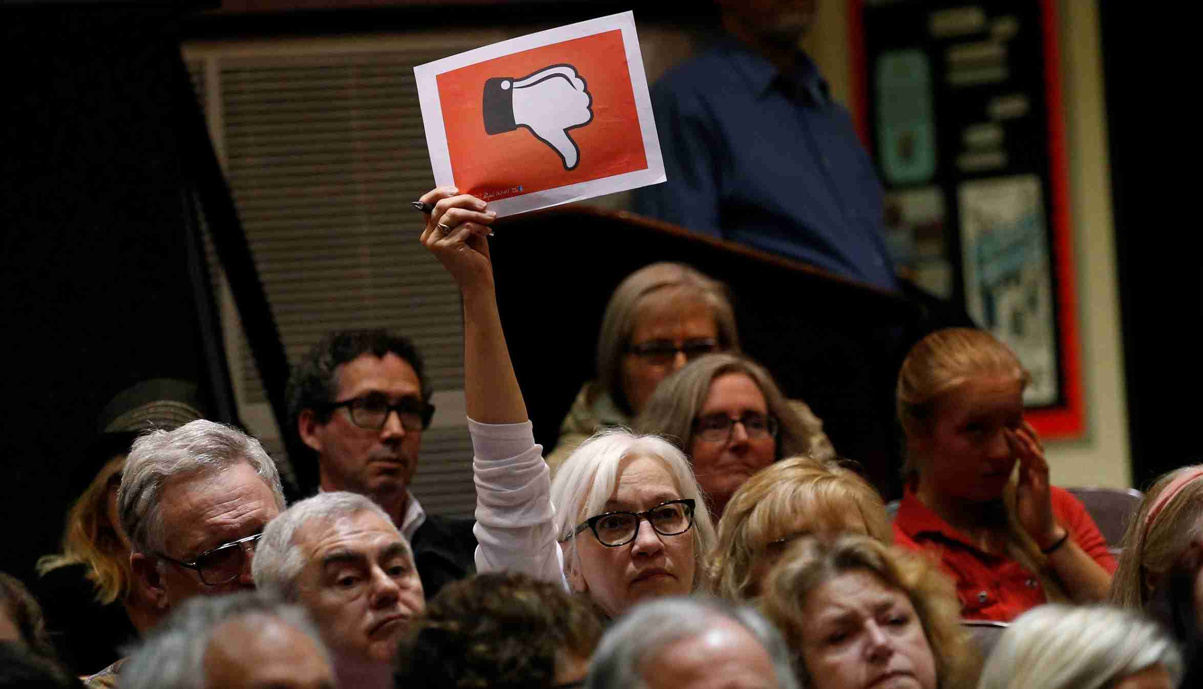 A voter holds up a sign during a town hall meeting with constituents by U.S. Representative Leonard Lance (R-NJ) in Cranford, New Jersey, U.S., May 30, 2017. REUTERS/Mike Segar - RTX38ALZ
