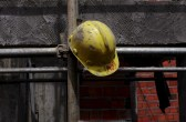 A worker's helmet hangs on scaffolding.