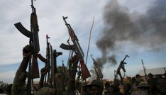 Rebel fighters hold up their rifles as they walk in front of a bushfire in a rebel-controlled territory in Upper Nile State, South Sudan February 13, 2014. South Sudan's rebels said on Tuesday that government soldiers had launched attacks against their positions in oil-rich Unity State in what they said was a violation of a peace deal signed in August. Picture taken February 13, 2014. REUTERS/Goran Tomasevic TPX IMAGES OF THE DAY - RTS7JEQ