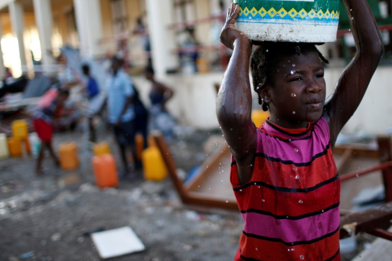 A girl carries a plastic container filled with water in a partially destroyed school used as a shelter after Hurricane Matthew hit Jeremie, Haiti, October 12, 2016. REUTERS/Carlos Garcia Rawlins - S1BEUGPVGKAA