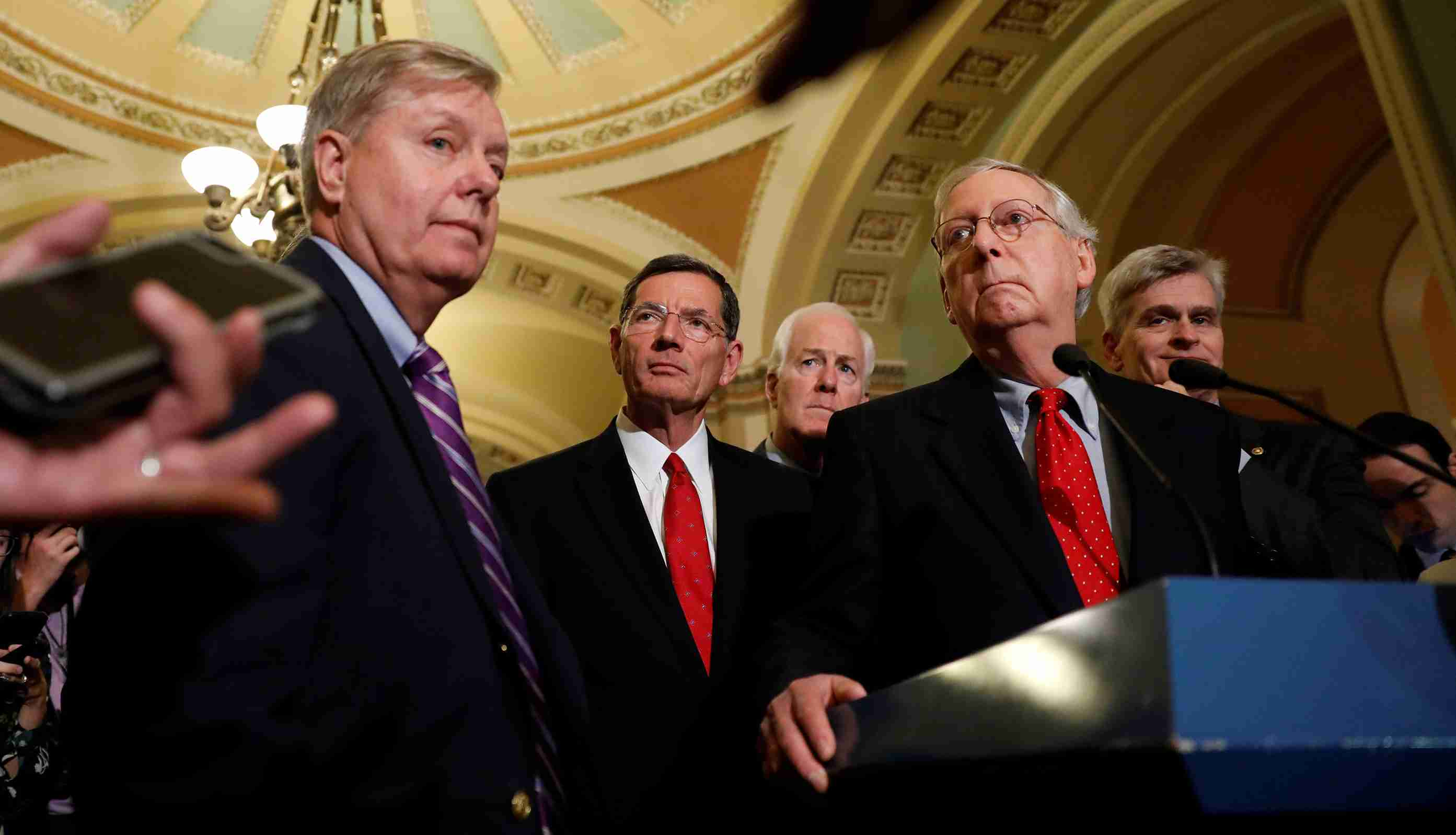 Senate Majority Leader Mitch McConnell, accompanied by Sen. Lindsey Graham (R-SC), Sen. John Barrasso (R-WY), Sen. John Cornyn (R-TX) and Sen. Bill Cassidy (R-LA), speaks with reporters following the party luncheons on Capitol Hill.