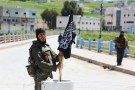 """A Nusra Front fighter carries a shell near a Nusra Front flag on his weapon in Jisr al-Shughour town, after rebels took control of the area April 25, 2015. Islamist insurgents including al-Qaeda's wing in Syria Nusra Front seized the strategic northwestern Syrian town of Jisr al-Shughour on Saturday, for the first time in the four year conflict. Syrian state media said the army had redeployed to the town's surroundings """"to avoid civilian casualties"""". Opposition fighters and the Syrian Observatory for Human rights said that the town was now totally controlled by the insurgents. REUTERS/Ammar Abdullah - GF10000072359"""