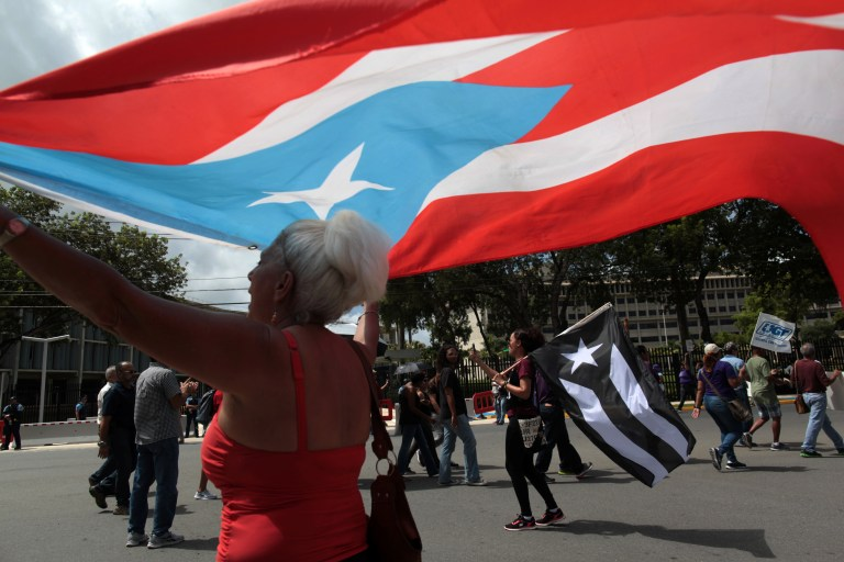 People protest in front of the federal court building where Puerto Rico's main creditors meet before a U.S. bankruptcy judge, in San Juan, Puerto Rico