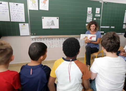 Children listen to their teacher on the first day of the new school year in a primary school in Nice