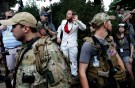 A white nationalist stands behind militia members after he scuffled with a counter demonstrator in Charlottesville, Virginia, U.S., August 12, 2017. REUTERS/Joshua Roberts - RC164F32C360