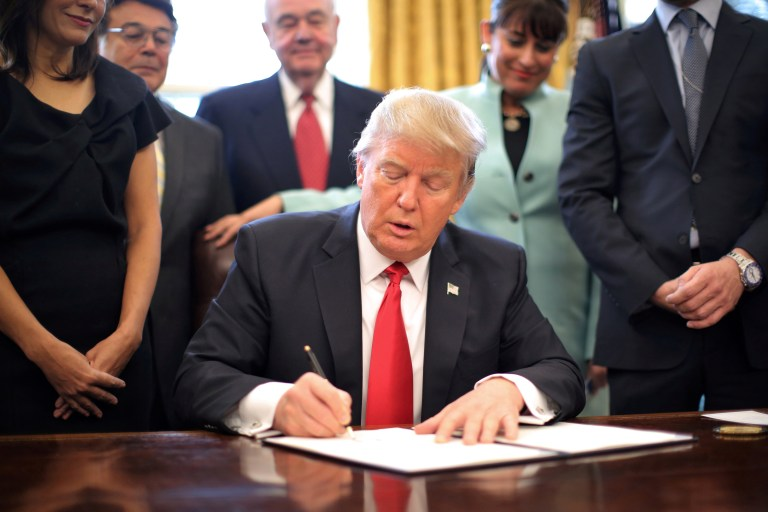 U.S. President Donald Trump signs an executive order.