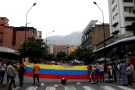 Opposition supporters build a barricade as they hold a Venezuelan national flag during a protest against Venezuela's President Nicolas Maduro in Caracas, Venezuela July 10, 2017. REUTERS/Marco Bello - RC1F513D6400