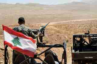 Lebanese Army soldiers ride on their military vehicles in Ras Baalbek