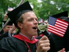 Regan Grabner waves a U.S. flag with a dollar bill tied to it as he graduates from Harvard's Business School during the 357th Commencement Exercises at Harvard University in Cambridge