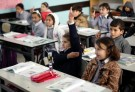 Palestinian first-graders sit with their schoolbook