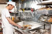 Fry cook cooking burgers in a commercial fast food restaurant kitchen