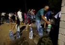 People queue to collect water from a spring in the Newlands suburb as fears over the city's water crisis grow in Cape Town, South Africa, January 25, 2018. Picture taken January 25, 2018. REUTERS/Mike Hutchings - RC171131EE10