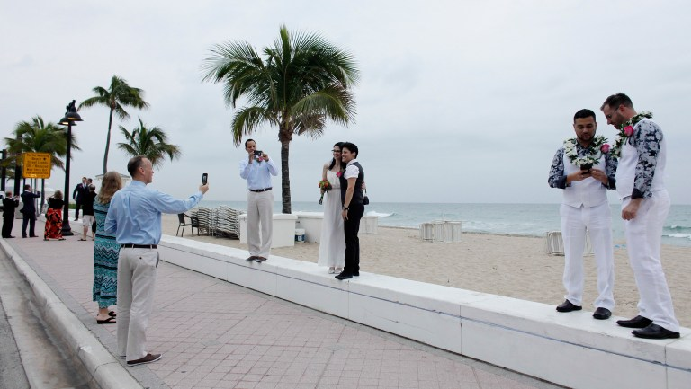 Couples take photographs in Fort Lauderdale, Florida.