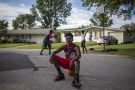 "Randy Johnson, 17, a high school student, poses for a portrait between games of basketball outside a friend's residence in Ferguson, Missouri July 21, 2015. When asked how Michael Brown's death affected him, Johnson said, ""I don't trust the law anymore. I could be next."" When asked what changes he has seen in his community over the past year, Johnson said, ""The police don't come around no more. They don't want an incident like that."" On August 9, 2014 a white police officer shot unarmed black teenager Michael Brown dead in the St. Louis suburb of Ferguson, Missouri."