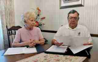 Retired engineer and his wife look over documents concerning their investments at their home in Orlando.