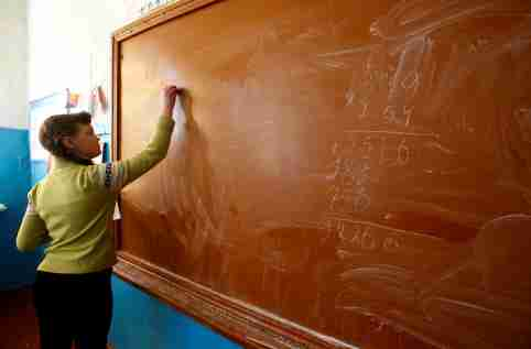 A child practices algebra on a chalk board.