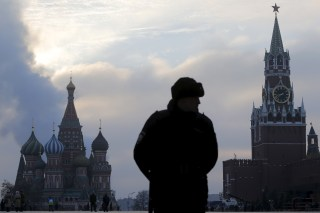 An Interior Ministry member stands guard on Red Square with parts of the Kremlin seen in the background.
