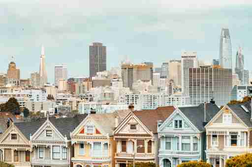 painted ladies victorian houses and san francisco skyline at background