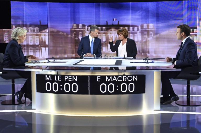 (From L) French presidential election candidate for the far-right Front National (FN) party, Marine Le Pen, French journalist Christophe Jakubyszyn, French journalist Nathalie Saint-Cricq and French presidential election candidate for the En Marche ! or Onwards ! movement, Emmanuel Macron pose prior to the start of a live broadcast face-to-face debate in television studios of French public national television channel France 2, and French private channel TF1 in La Plaine-Saint-Denis, Paris, France, May 3, 2017. REUTERS/Eric Feferberg/Pool - UP1ED531JT6BW