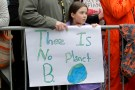 A girl holds a sign saying There is no planet B.