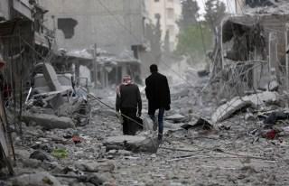 Men walk through debris in the center of Afrin, Syria March 24, 2018. REUTERS/Khalil Ashawi - RC1850B1E4F0