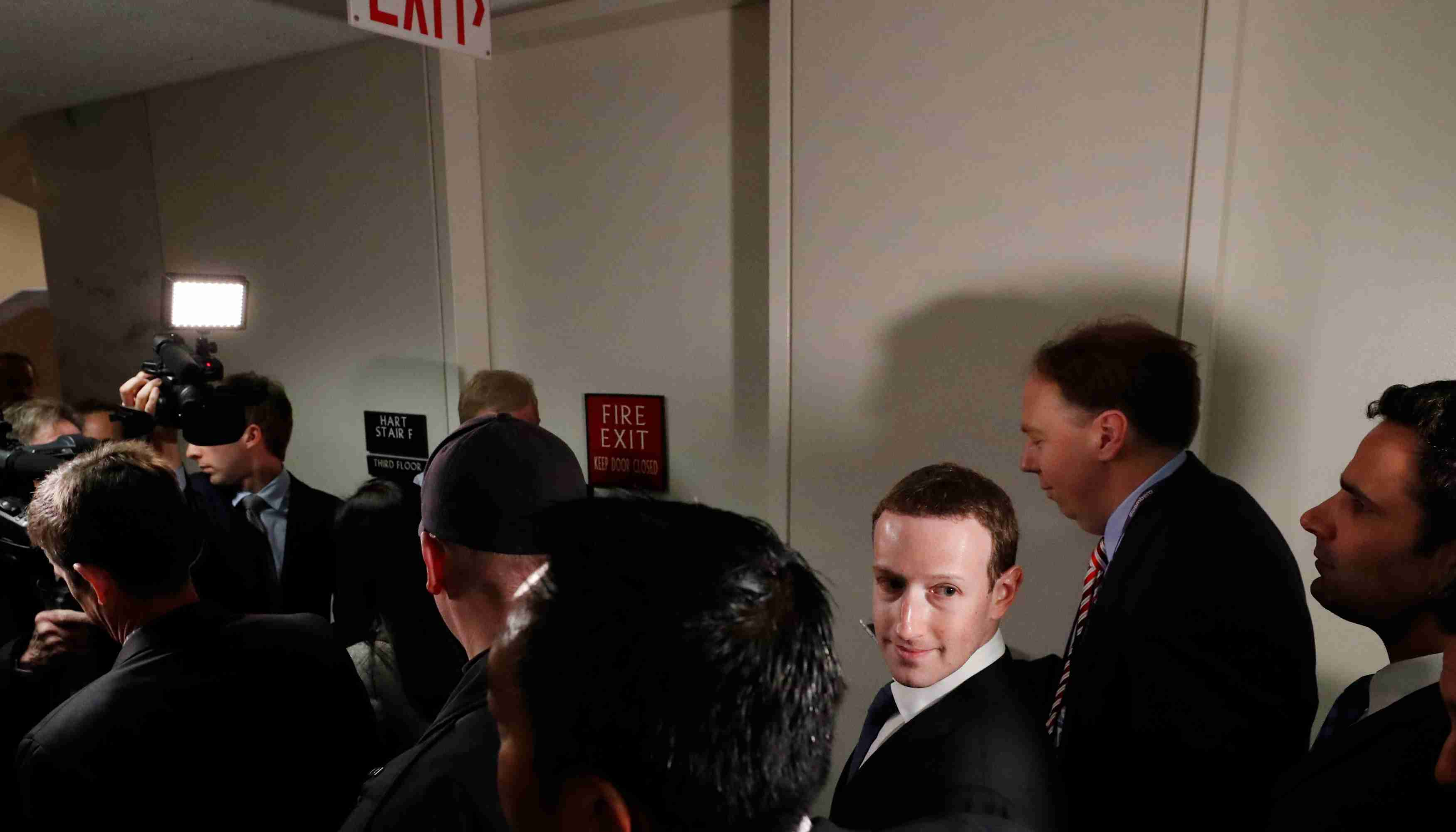 Members of the media (L) keep pace with Facebook CEO Mark Zuckerberg