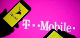 A smartphones with Sprint logo are seen in front of a screen projection of T-mobile logo.