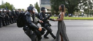 Lone activist Ieshia Evans stands her ground while offering her hands for arrest as she is charged by riot police during a protest against police brutality outside the Baton Rouge Police Department in Louisiana, USA, 9 July 2016. Evans, a 28-year-old Pennsylvania nurse and mother of one, traveled to Baton Rouge to protest against the shooting of Alton Sterling. Sterling was a 37-year-old black man and father of five, who was shot at close range by two white police officers. The shooting, captured on a multitude of cell phone videos, aggravated the unrest coursing through the United States in previous years over the use of excessive force by police, particularly against black men. REUTERS/Jonathan Bachman   TPX IMAGES OF THE DAY - RC1F5C88B300