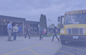 Children walking into school from a bus