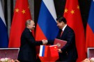 Russia's President Vladimir Putin (L) and China's President Xi Jinping shake hands after signing an agreement during a bilateral meeting at the Xijiao State Guesthouse ahead of the fourth Conference on Interaction and Confidence Building Measures in Asia (CICA) summit, in Shanghai May 20, 2014. Trade between China and Russia is expected to reach $100 billion by 2015, Xi said on Tuesday, after meeting with Putin. REUTERS/Carlos Barria  (CHINA - Tags: POLITICS BUSINESS) - GM1EA5K14XV01
