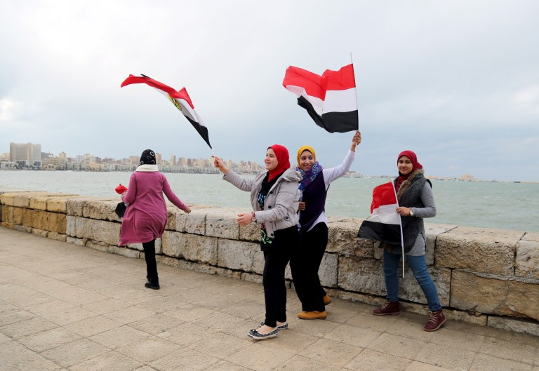 Pro-government protesters chant slogans while holding Egyptian national flags as they walk near the seaside on the fifth anniversary of the uprising that ended the 30-year reign of Hosni Mubarak in Alexandria, Egypt, January 25, 2016. REUTERS/Asmaa Waguih - RTX23Y78