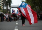 A person carries a Puerto Rican national flag during a protest against the government's austerity measures as Puerto Rico faces a deadline on Monday to restructure its $70 billion debt load or open itself up to lawsuits from creditors, in San Juan, Puerto Rico May 1, 2017. REUTERS/Alvin Baez - RC1B567AF880