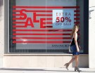 A woman walks past a sign advertising a sale in the Old Town shopping area of Pasadena, California, U.S. June 27, 2017.  REUTERS/Mario Anzuoni - RC16547F38A0
