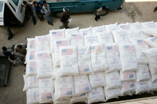 People stand beside a truck loaded with sacks of flour received from The United States Agency for International Development (USAID).