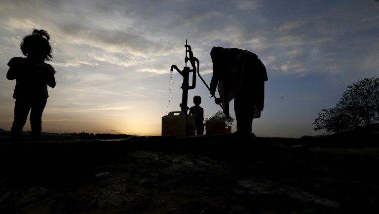 A woman draws water from a well in a slum on the outskirts of Islamabad March 30, 2015. REUTERS/Caren Firouz - GF10000043990