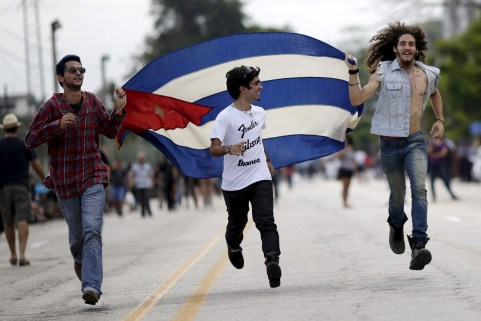 Fans run with a Cuban flag outside Ciudad Deportiva de la Habana sports complex where the Rolling Stones' free outdoor concert will take place today in Havana, March 25, 2016. REUTERS/Ueslei Marcelino      TPX IMAGES OF THE DAY      - GF10000360577