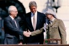 PLO Chairman Yasser Arafat (R) shakes hands with Israeli Prime Minister Yitzhak Rabin (L), as U.S. President Bill Clinton stands between them, after the signing of the Israeli-PLO peace accord, at the White House in Washington September 13, 1993. REUTERS/Gary Hershorn (UNITED STATES - Tags: POLITICS) - GM1E99D1UCD01