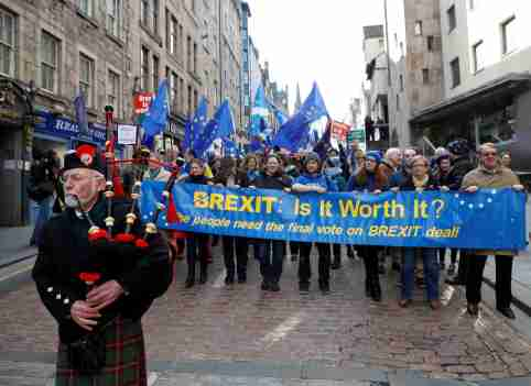A piper leads protesters waving Saltires and EU flags as they take part in a demonstration to demand a vote on the Brexit deal between Britain and the European Union in Edinburgh, Scotland, March 24, 2018. REUTERS/Russell Cheyne - RC13724D73C0