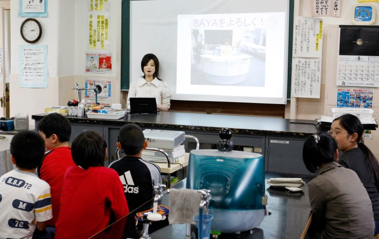 "A humanoid robot named ""Saya"" (C) speaks to school pupils as she takes on a role as a school teacher, during a demonstration at an elementary school in Tokyo May 7, 2009. The robot, developed by the Tokyo University of Science professor Hiroshi Kobayashi, which can speak different languages, make facial expressions like happiness, surprise, sadness, fear, anger or disgust with motors inside her face. REUTERS/Issei Kato (JAPAN SCI TECH EDUCATION SOCIETY) - GM1E5571L2O01"