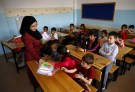 """A Syrian refugee teacher distributes books to her refugee students in their classroom at Fatih Sultan Mehmet School in Karapurcek district of Ankara, Turkey, September 28, 2015. Out of 640,000 Syrian children in Turkey, 400,000 are not at school, a Turkish official told Reuters on Friday, warning that those who miss out are likely to be exploited by """"gangs and criminals"""". Educating the children among more than 2.2 million Syrian refugees in Turkey - most of whom live outside purpose-built camps - is seen as a critical part of the humanitarian response to the four-and-a-half-year-old conflict. Picture taken September 28, 2015. REUTERS/Umit Bektas  - GF10000230197"""