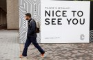 A man passes a sign promoting Crystal City where Amazon announced its new headquarters would be based in Arlington, Virginia, U.S., November 13, 2018. REUTERS/Kevin Lamarque - RC12EAD83090