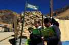 School girls walk in front of a sign at the ramshackle town of Morococha in the Andean city of Junin, June 18, 2012. High in the Andes mountain range, a Chinese mining company is now in the housing construction and demolition business as it works to relocate a Peruvian town that sits in the way of its $2.2 billion Toromocho copper mine. By late July, state-owned miner Chinalco says it will finish building a new city of paved roads and multi-story homes for 5,000 people currently living on the side of a giant red mountain of copper 15,000 feet (4,500 meters) above sea level. Picture taken June 18, 2012. To match Feature PERU-MINING/CHINALCO  REUTERS/Pilar Olivares (PERU - Tags: POLITICS ENVIRONMENT) - GM1E8711UBF01