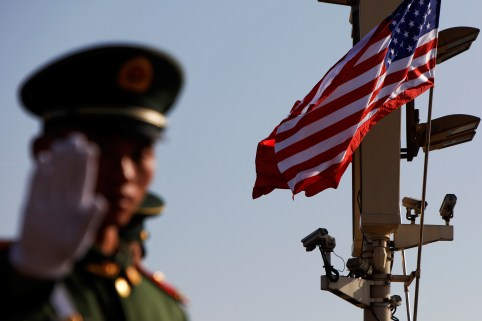 A paramilitary policeman gestures under a pole with security cameras, U.S. and China's flags near the Forbidden City ahead of the visit by U.S. President Donald Trump to Beijing, China November 8, 2017. REUTERS/Damir Sagolj - RC194AD3C400