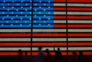 An Occupy Wall Street movement activist raises his fist while protesting in front of a digital flag of the United States in Manhattan's Time Square in New York on July 17, 2012.  REUTERS/Adrees Latif  (UNITED STATES - Tags: CIVIL UNREST SOCIETY) - GM1E87I0W6M01