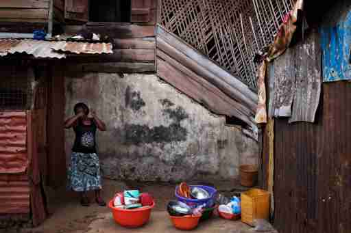 A woman combs her hair in the back courtyard of a traditional colonial-era Board House dating back about a century in the Murray Town neighbourhood of Sierra Leone's capital Freetown April 28, 2012.  Board Houses are a reconstruction of cabin-like structures built in the 18th century on the American eastern seaboard.  There were some modifications though, notably a three-foot base layer of porous local stone (seen here) that helped anchor the house down during Sierra Leone's torrential wet season.  Picture taken April 28, 2012.  REUTERS/Finbarr O'Reilly (SIERRA LEONE - Tags: SOCIETY)   ATTENTION EDITORS - PICTURE 06 OF 29 OF PACKAGE 'FREETOWN - FADING ARCHITECTURE' - GM1E8531KOM01