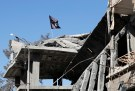 A flag of Islamic State militants is pictured above a destroyed house near the Clock Square in Raqqa, Syria October 18, 2017. Picture taken October 18, 2017.     REUTERS/Erik De Castro - RC159E696010