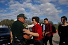 Alfonso Calderon (C), a student who was at Marjory Stoneman Douglas High School during the mass shooting, greets the police officer Brad Griesinger in front of the school, after the police security perimeter was removed, in Parkland, Florida, U.S., February 18, 2018. REUTERS/Carlos Garcia Rawlins - RC1735C2F100